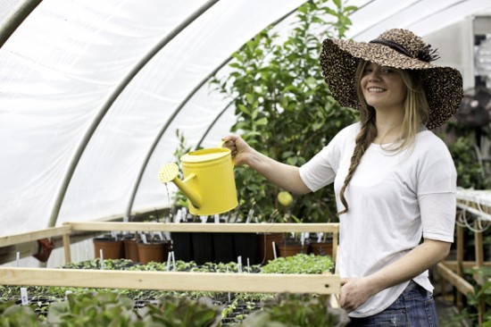 Sarah Nuhmeyer in greenhouse with hat and watering can