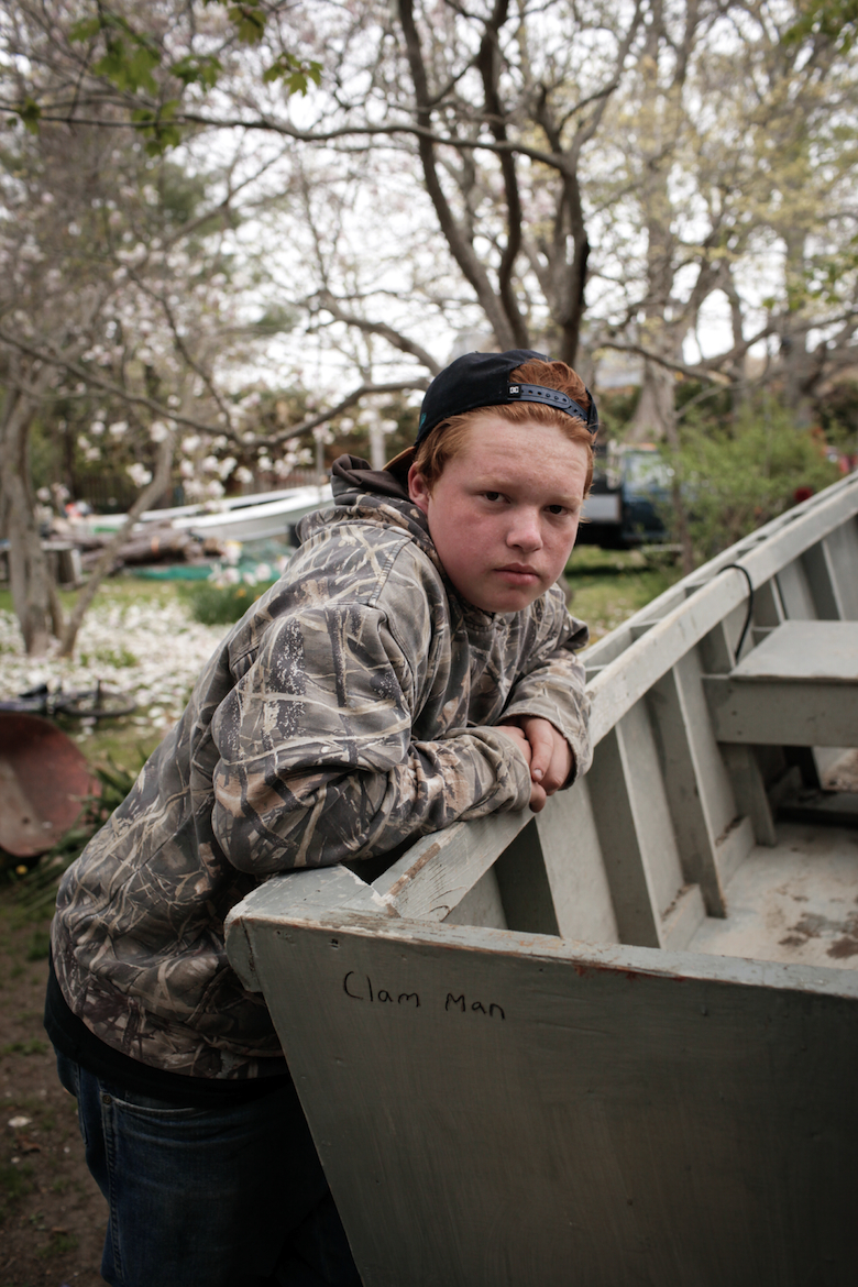 "Will, age 12, sitting in front of his boat named ""Clam Man"".  He reinvests the money made from fishing into the boat he purchased himself and on new gear. (2015)"