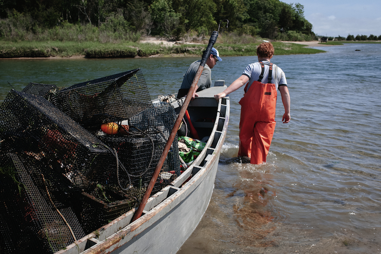 Will with family friend Justin navigating low tide in Springs.  They didn't have much success in the location where they first set these eel traps so decided to relocated them across the harbor. (2015)