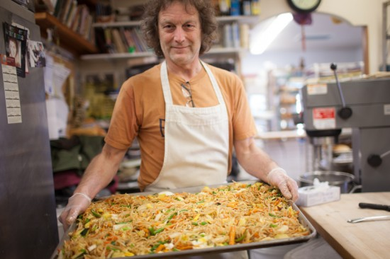 Brad Thompson displays a tray of stir fried noodles. His partner Nancy is behind the bagels although he sources the salmon.