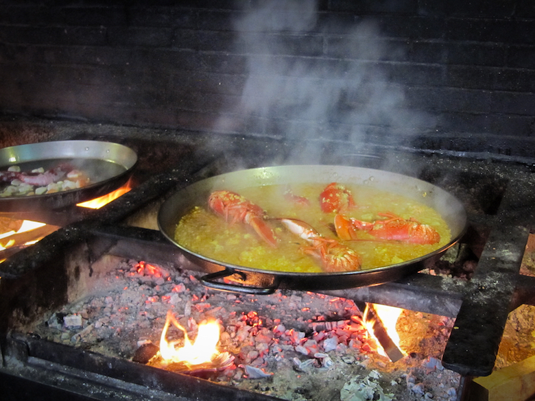 Paella cooking on a wood-burning stove.