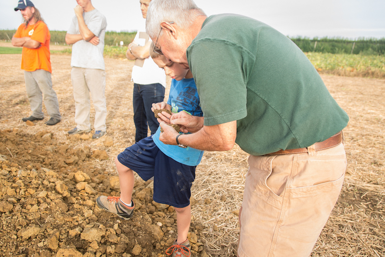 John Halsey discusses the soil with his grandson and self professed future farmer.